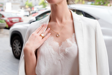 People, fashion, jewelry and luxury concept, closeup of woman wearing luxury jewelry standing near expensive car on the street. Color gemstone ring and pendant with colored diamonds and gemstones