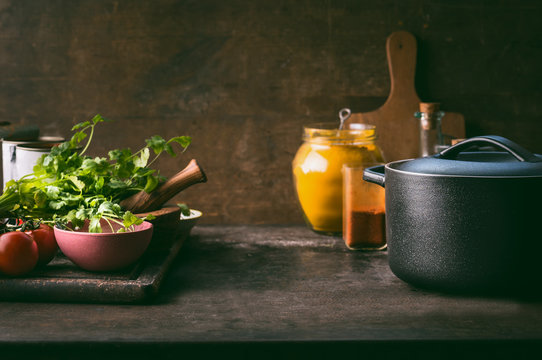 Food background with cast iron cooking pot, fresh seasoning and spices on rustic kitchen table. Copy space. Healthy eating, clean food concept