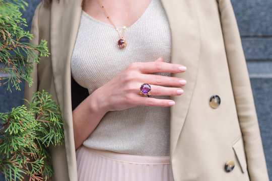 People, fashion, jewelry and luxury concept, closeup of woman wearing luxury jewelry standing on the street. Color gemstone ring and pendant with colored diamonds and gemstones
