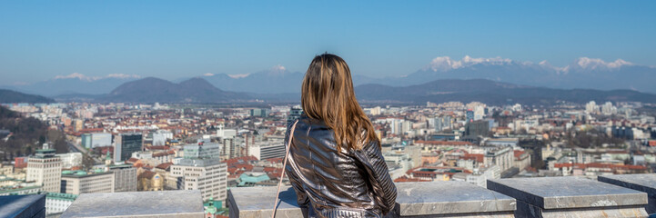 View from behind of a woman standing on top of Ljubljana castle