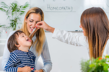 Homeopathy. Mother and little boy visiting a homeopath Wall mural