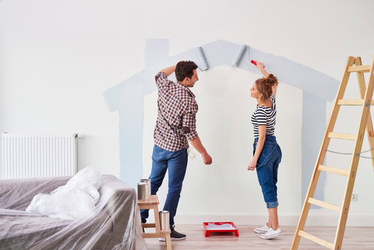 Young couple painting the interior wall in their new apartment