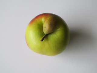 shy red and green apple with a woody stalk