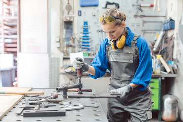 Female mechanic working with clamp and spanner on workpiece