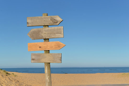 wooden signs on a post in a beach under blue sky