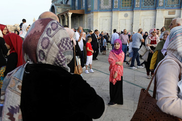 A Palestinian girl poses for her relative to photograph her after Eid al-Fitr prayers which marks the end of the holy fasting month of Ramadan, on the compound known to Muslims as Noble Sanctuary and to Jews as Temple Mount in Jerusalem's Old City