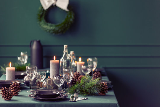 Elegant dining room table with wine glasses, plates and candles set for christmas dinner