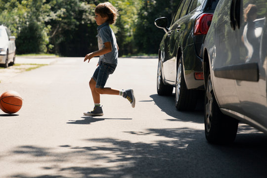 Careless boy running behind the ball on the road next to cars