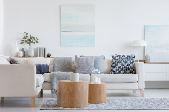 Two wooden coffee tables with plant in pot in front of grey corner sofa in fashionable living room interior