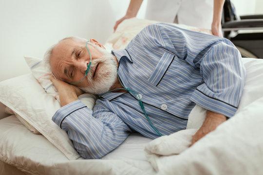 Sick elderly man wearing blue pajama lying in bed at nursing home