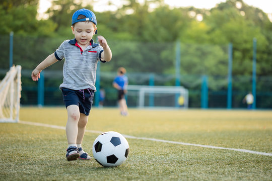 young little kid 3 or 5  years old enjoying happy playing football soccer at grass city park field posing smiling proud standing holding the ball in childhood sport passion and healthy lifestyle