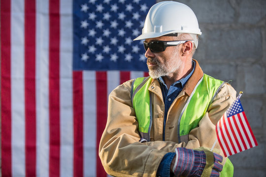 American builder looking sideways with stars and stripes flag in background