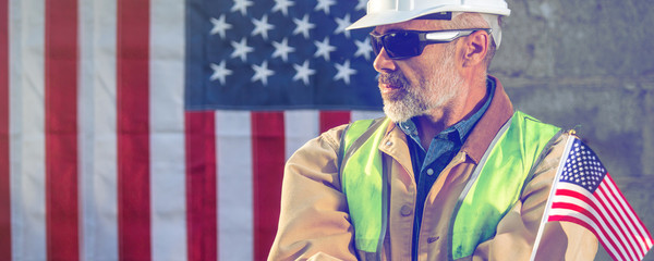 American worker  builder looking sideways with stars and stripes flag in background, wide image, toned