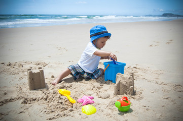 A child (baby boy) playing on a beach with sand and toys