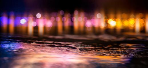 Dark street of the night city. Abstract bokeh light. Reflection on the wet asphalt, the lights of the night city. Dark background with abstract bokeh, rays of light.