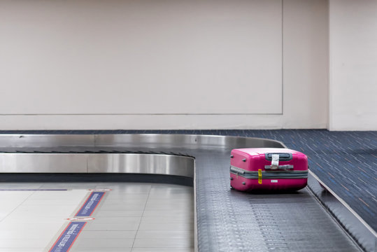 Pink laggage on the coveyor at the airport.