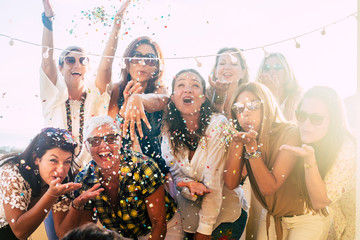 Group of people celebrate together having a lot of fun blowing coloured confetti - friendship and diversity ages generation laugh and smile on party - cheerful joyful concept for ladies Wall mural