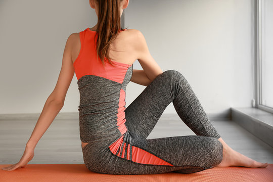 Young sporty woman practicing yoga in gym