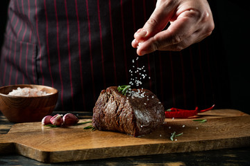 Chef hands cooking meat steak and adding salt and pepper on black copy space background for menu restaurant or recipe text.