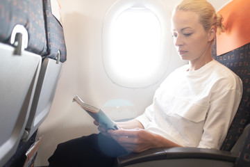 Woman reading in flight magazine on airplane. Female traveler reading seated in passanger cabin. Sun shining trough airplane window.