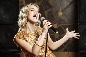 Beautiful young woman singing with the microphone Fotobehang