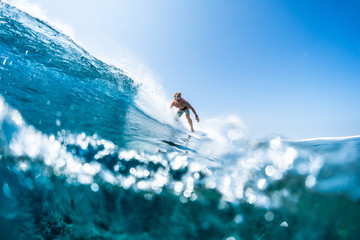 Wall Mural - Surfer rides tropical, crystal clear ocean wave