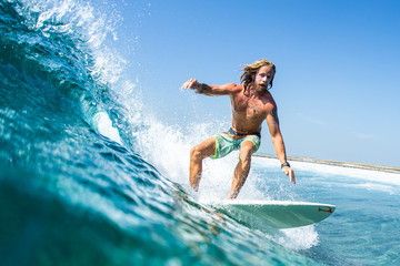Caucasian, long haired surfer rides the ocean wave on the Jailbreaks surf spot in Maldives