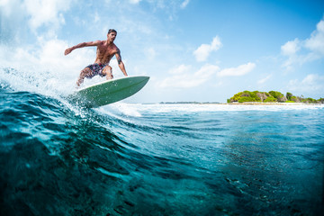 Wall Mural - Young surfer with lean muscular body rides the tropical wave