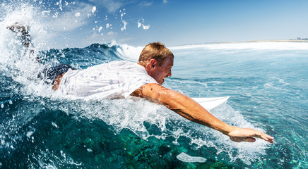 Surfer paddles hard in his attempt to catch the wave