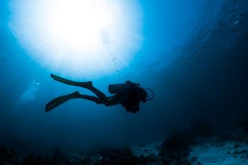 Silhouette of the scuba diver swimming alone in the depth