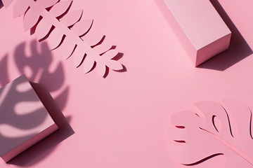 Paper tropical plants leaves on the pink background. Summer concept Top view