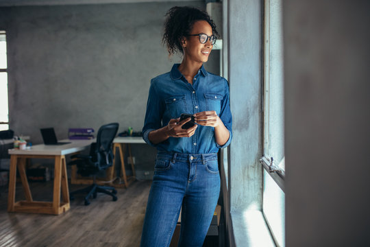 Woman looking out of a window in office