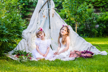 Two sisters in white dresses sit in white boho tent outdoor.