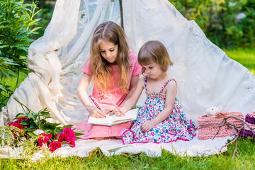 Two sisters in multi-colored dresses sit in white boho tent outdoor and draw in sketchbook.