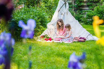 Two sisters in multi-colored dresses sit in white boho tent outdoor and draw in sketchbook. Flowers out of focus in the foreground.