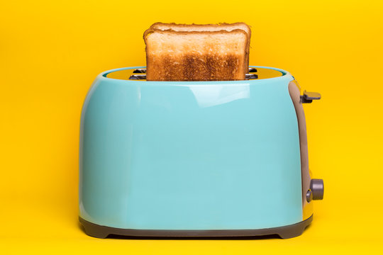 cyan color toaster on a yellow background