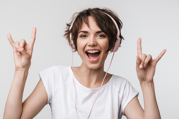 Wall Mural - Pretty excited happy woman posing isolated over white wall background listening music with headphones.