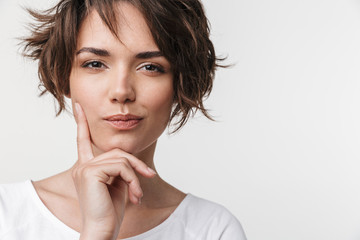 Beautiful young pretty thinking thoughtful woman posing isolated over white wall background.