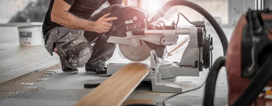 Handwerker schneidet Holzdiele mit der Kappsäge auf der Baustelle und die Späne werden direkt vom Staubsuager abgesaugt