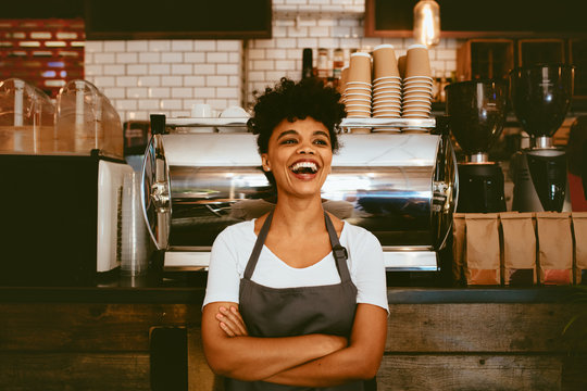 Cheerful barista in her coffee shop