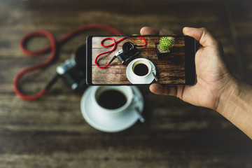 Hand holding smart phone taking photo of coffee and camera on wooden table.