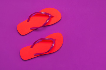 Wall Mural - Coral flip flops on purple background. Flat lay, top view, copy space. Creative Summer Vacation travel Background. Women's summer footwear. Bright flip flops, trend colors