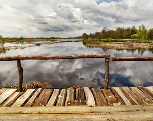 Old rough wooden footbridge by the lake in the forest. Thunderclouds reflected in the water of the lake. forest