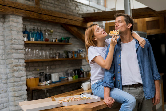 Young couple in love eating pizza in the rustic home