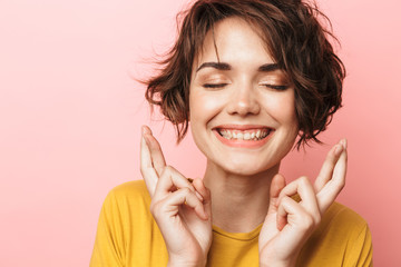 Wall Mural - Excited beautiful woman posing isolated over pink wall background make hopeful please gesture fingers crossed.