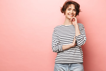 Wall Mural - Happy beautiful woman posing isolated over pink wall background.