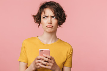 Wall Mural - Confused young beautiful woman posing isolated over pink wall background using mobile phone.