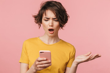 Wall Mural - Shocked young beautiful woman posing isolated over pink wall background using mobile phone.