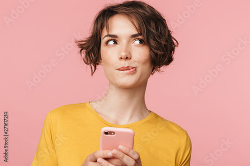 Wall mural Thinking dreaming young beautiful woman posing isolated over pink wall background using mobile phone.