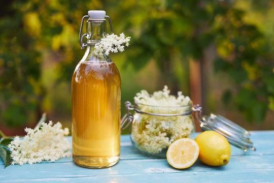 Bottle of elderflower syrup and elderberry flowers on wooden table